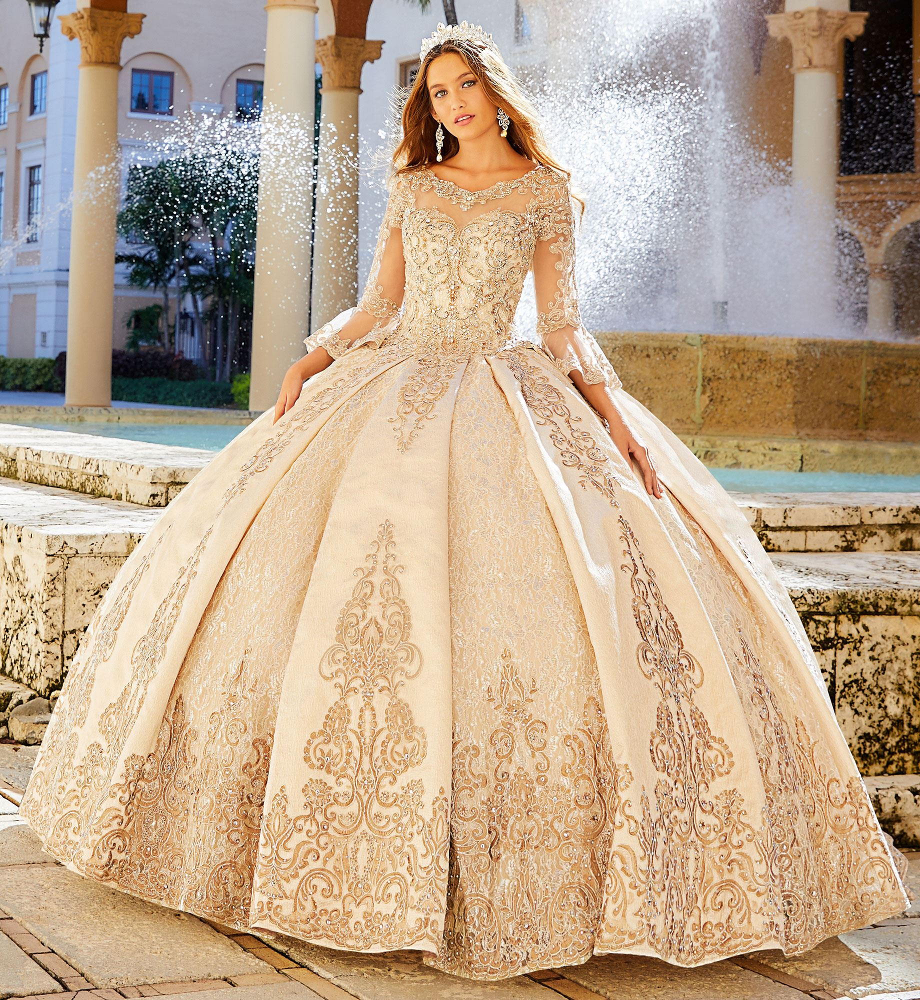 Brunette model in long sleeve sparkly gold quinceañera dress