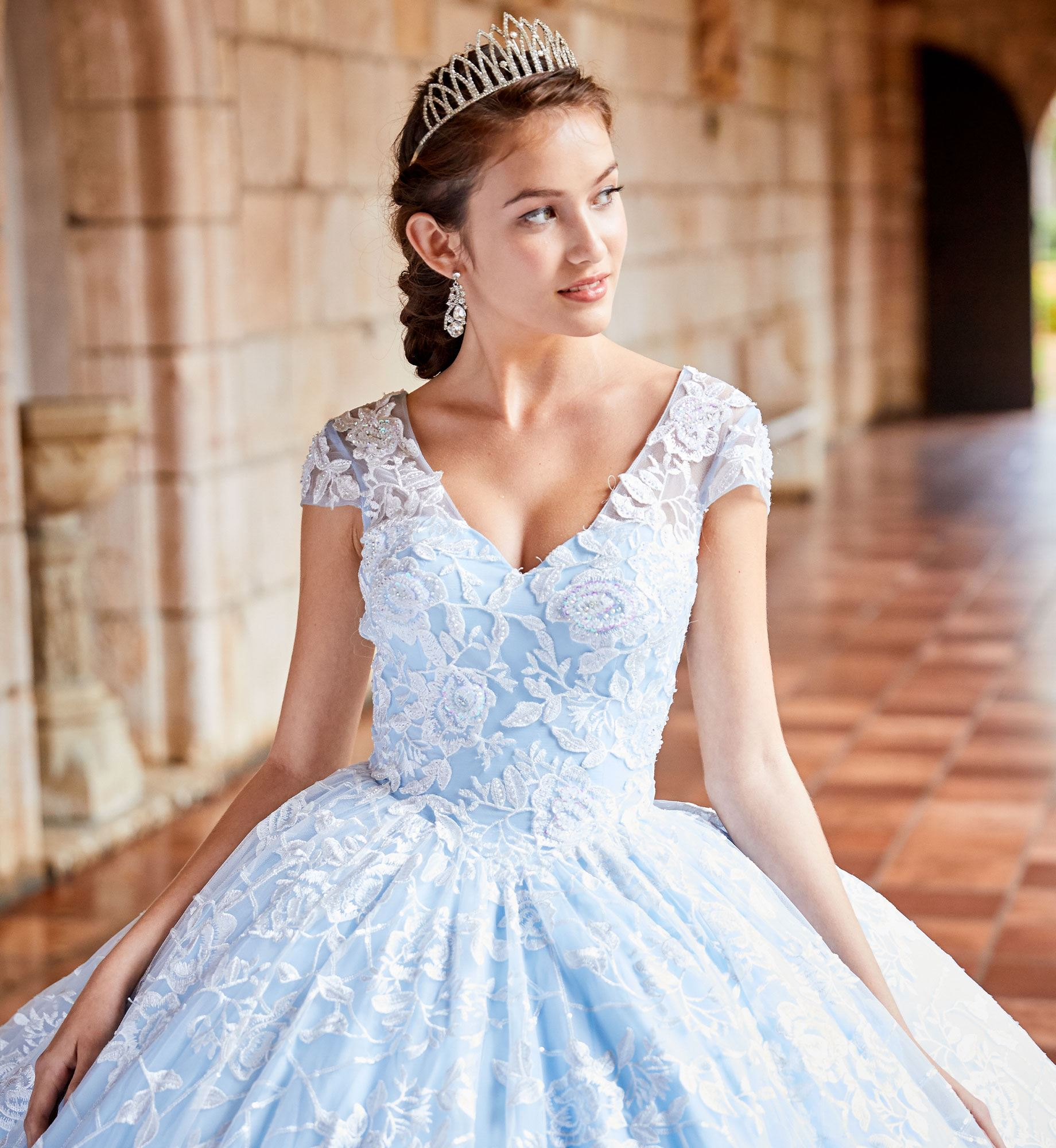 Brunette model in short sleeve blue quinceañera dress